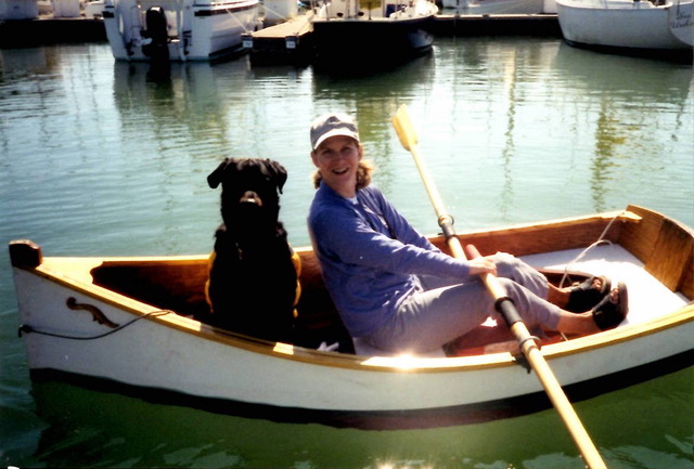 Woman and black dog in a row boat
